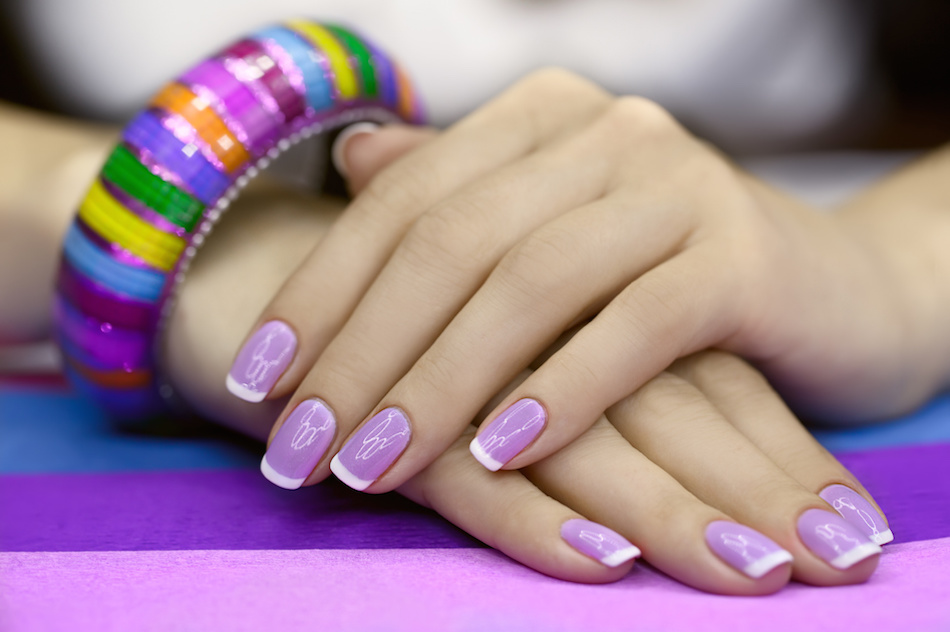 Beautiful women's manicure with purple polish on the nails